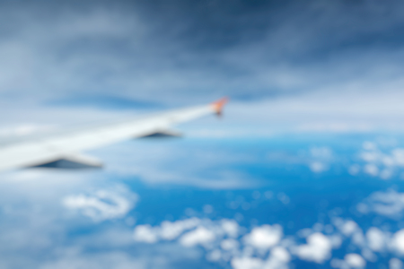 Out of Focus of Wing of an airplane flying above the clouds see through the window. Business concept.
