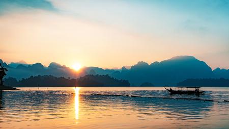 Silhouettenbild eines Bootes, das morgens in einem Damm im Süden Thailands segelt. Standard-Bild
