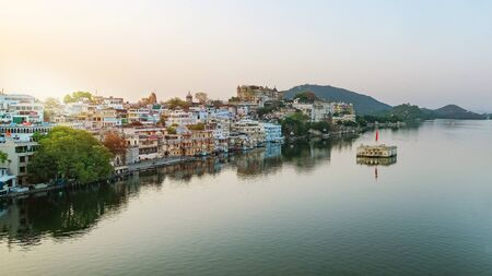 Udaipur city at lake Pichola in the morning, Rajasthan, India. View of City palace reflected on the lake.