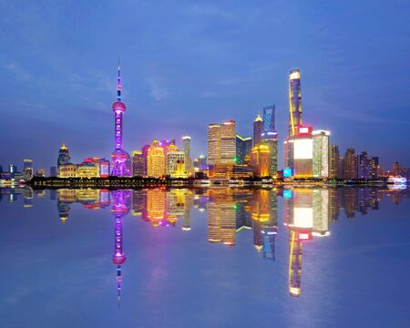Shanghai city skyline Pudong side looking through Huangpu river on twilight time. Shanghai, China. Beutiful vibrant panoramic image. Stock Photo