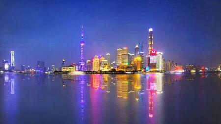 Shanghai city skyline Pudong side looking through Huangpu river on twilight time. Shanghai, China. Beautiful vibrant panoramic image.