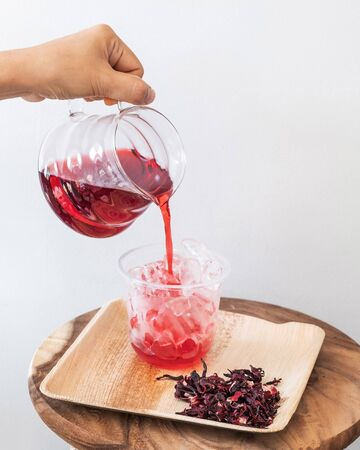 Ice roselle juice isolated on wooden tray and white background.