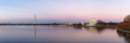 Blur background of Jefferson Memorial and Washington Monument reflected on Tidal Basin in the evening, Washington DC, USA. Panoramic image