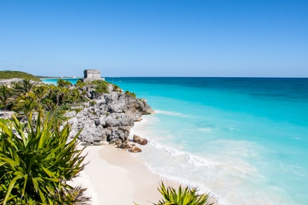 Beautiful beach with turquoise water  in Tulum Mexico, Mayan ruins on top of the cliff