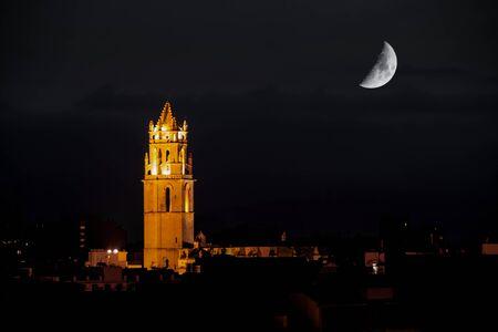 iluminated: Vista nocturna de un campanario rom�nico iluminado, y la mitad de la luna en el fondo