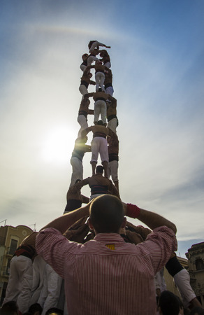 traditional climbing: REUS, SPAIN - OCTOBER 25, 2014: Castells Performance, a castell is a human tower built traditionally in festivals within Catalonia. This is also on the UNESCO Intangible Cultural Heritage of Humanity