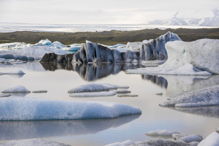 originated: Water reflections in Iceberg in Jokulsarlon glacier lake in Iceland. The icebergs originated from the Vatnajokull float. This location was used for various action movies.