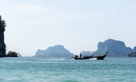 insular: A longtail motor boat in blue tropical waters, Railay beach in Thailand. Stock Photo