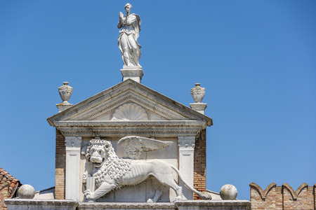 winged lion: The winged lion of St. Mark on top of The Porta Magna at the Venetian Arsenal. Is the symbol of the city of Venice in Italy and is often seen holding a book representing power, wisdom and justice Stock Photo