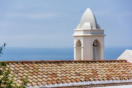 bb: Church Bell tower against a blue mediterranean sea in Bb Stock Photo