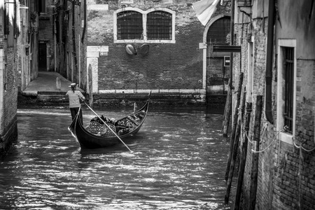punting: Venetian gondolier punting gondola through canal waters of Venice Italy. Black and white image Stock Photo