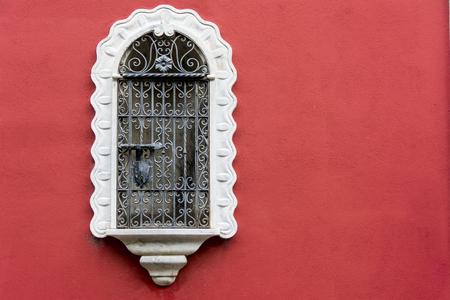 rejas de hierro: Ventana medieval antiguo con barras de hierro blanco y pared roja Foto de archivo