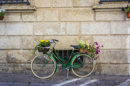 Groene uitstekende fiets met bloemen op de mand die op een muur leunt.