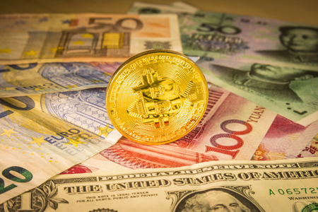 Golden bitcoin coin over Dollar, euro and yuan bills. Financial concept. Situation of Bitcoin and other cryptocurrencies in the real world