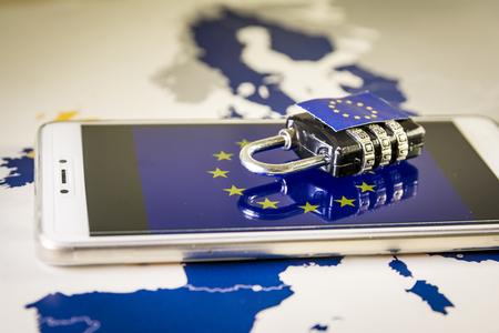 Vorhängeschloss über ein Smartphone und eine EU-Karte, die die EU-Datenschutzgrundverordnung oder DSGVO symbolisieren. Entwickelt, um die Datenschutzgesetze in Europa zu harmonisieren. Standard-Bild