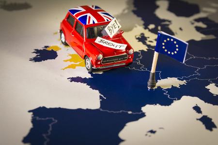 Auto d'epoca rossa con bandiera Union Jack e brexit o ciao parole su una mappa e bandiera dell'UE. Archivio Fotografico - 91947311