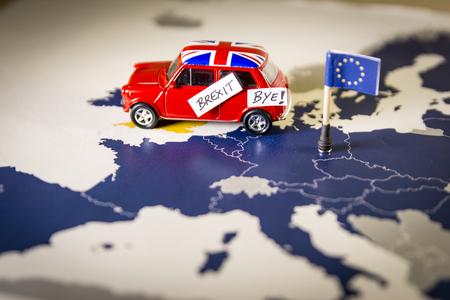 Carro vermelho do vintage com bandeira de Union Jack e palavras do brexit ou do adeus sobre um mapa e uma bandeira de UE. Foto de archivo