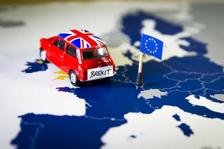 Coche rojo de la vendimia con la bandera de Union Jack y brexit o adiós palabras sobre un mapa de UE y una bandera.