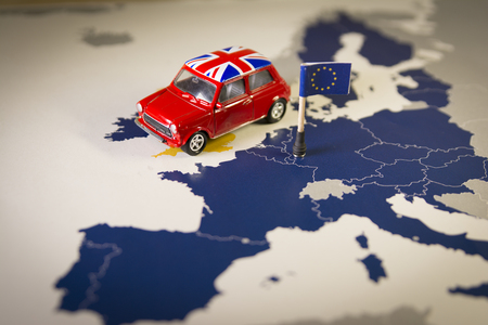 Red vintage car with Union Jack flag over an UE map and flag.