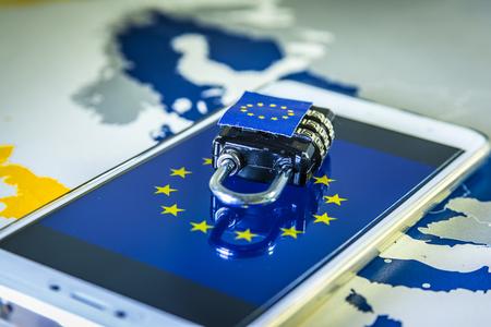 Hangslot boven een smartphone en EU-kaart, symbool van de EU Algemene Verordening Gegevensbescherming of GDPR. Ontworpen om de wetgeving inzake gegevensprivacy in heel Europa te harmoniseren. Stockfoto