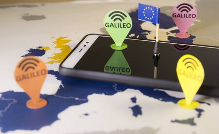 Toy car, Galileo pin and a smartphone Over a EU map. Galileo system metaphor Foto de archivo