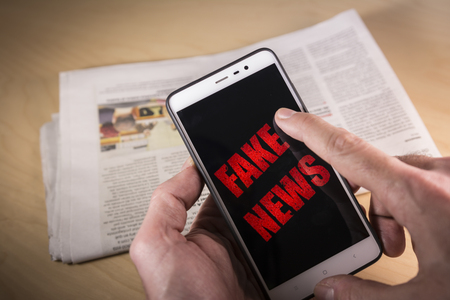 Hand holding a Smartphone with red Fake News words on screen and a newspaper on the background HOAX and Fake news concept. Stock Photo