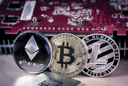 Financial concept with physical bitcoin, ethereum and Litecoin with a Video card.