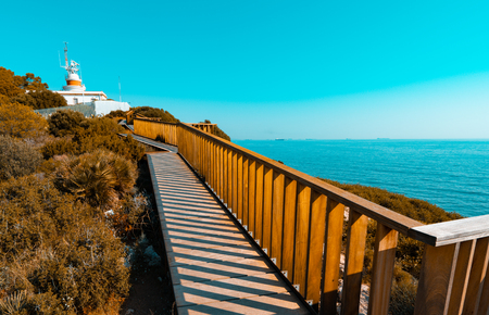Vanishing point to old lighthouse of Salou in Costa Daurada. Mediterranean sea coast in Spain. Orange and teal style.