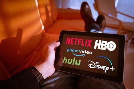 Barcelona, Hiszpania. Styczeń 2019: Mężczyzna trzyma tablet z logo Netflix, hulu, amazon video, HBO i Disney na ekranie Publikacyjne