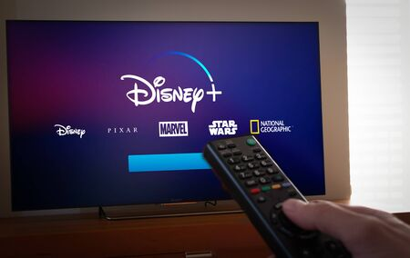 Barcelona, Spain. January 2019: Man holds a remote control With Netflix, HBO and the new Disney logos on TV screen