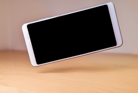 Smartphone device floating or levitating over a wooden table Stock fotó