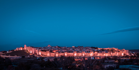 Panoramic night view of the historic city of Avila. UNESCO World Heritage. Orange and teal color