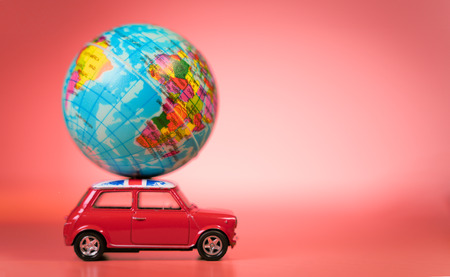 Miniature Toy vintage car carrying a world map balloon.Travel and transport concept. Stock Photo