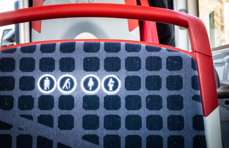 Close up of round icon priority seat for elderly, pregnant or disabled people on a bus seat in Barcelona