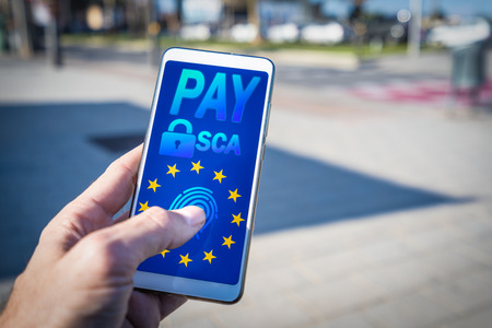 Hands using a smartphone with SCA payment on screen.