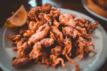 Spanish tapas: Plate of deep fried squids or Chipirones with lemon.