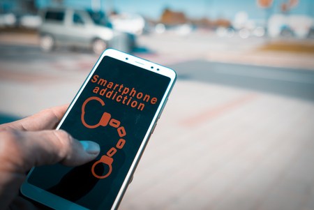 Hands using a smartphone with handcuffs and smartphone addiction words on screen