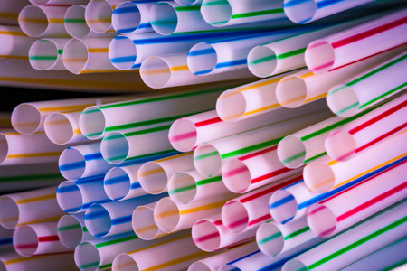 Background of colourful plastic straws as an environmental problem.