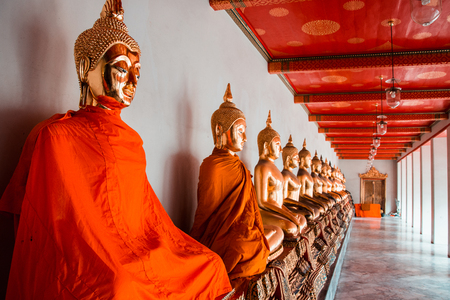 Row of golden meditation buddha sitting figures statues in Wat Pho temple in Bangkok