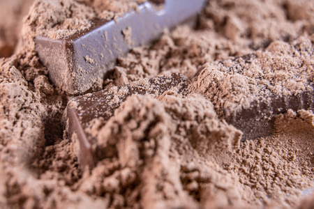 Milk sweet chocolate bar on chocolate powder