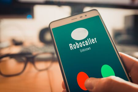 Smartphone showing a call from a robocaller on screen Banco de Imagens