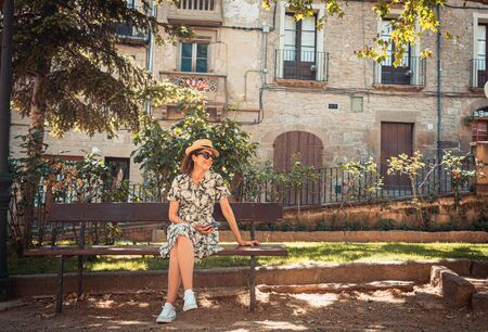 tourist woman sitting on a bench in the medieval town of Solsona