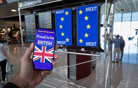 Hand holding a smartphone with UK boarding pass on the screen and EU flag on the info panels representing the Brexit.