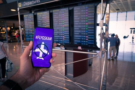 Hand holding a smartphone with Flyskam message on screen with airport timetables as background.