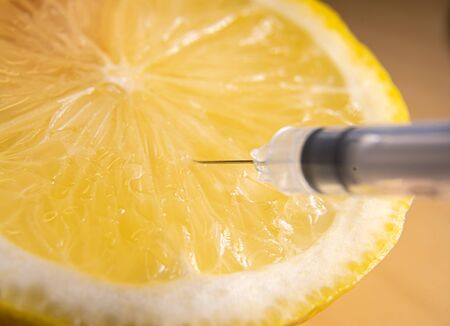 Syringes or needles extracting vitamin C from lemon.