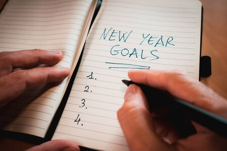hand writing new years resolutions in a notebook