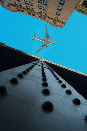 Looking up view of cast iron buildings in New York City with an airplane over a blue sky. 스톡 콘텐츠