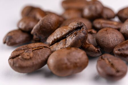 Brown roasted coffee beans on white background.