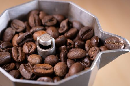 Coffee beans in an italian espresso coffee pot. Morning coffee and relaxing time. Macro shot.