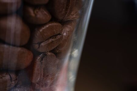 Brown roasted coffee beans inside a glass jar